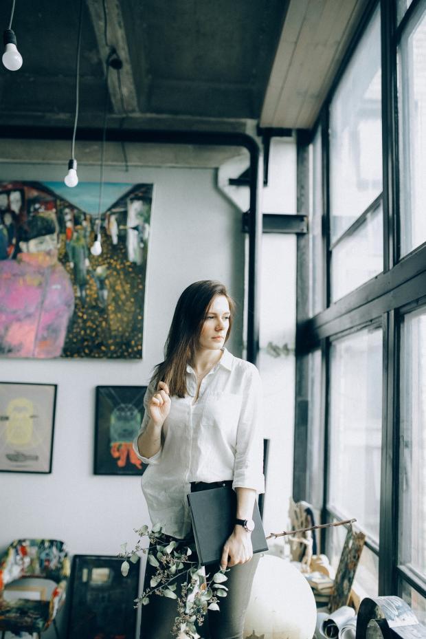 женщина в белой блузке стоит у большого окна