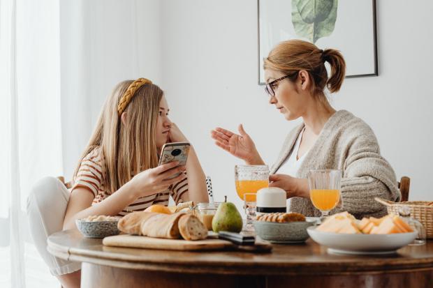 мама разговаривает с дочерью за столом