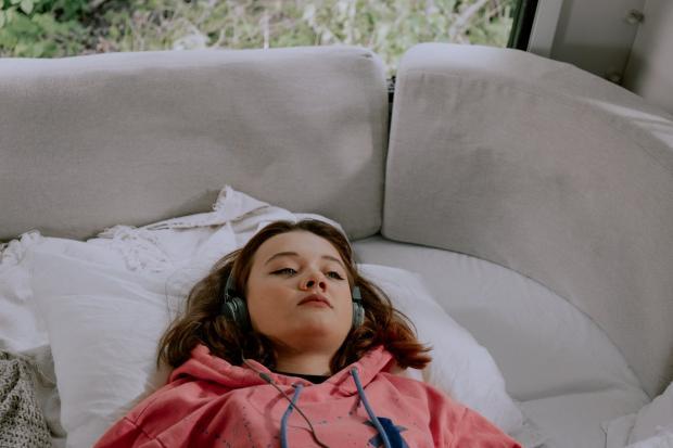 девочка-подросток лежит на белом диване и слушает музыку в наушниках