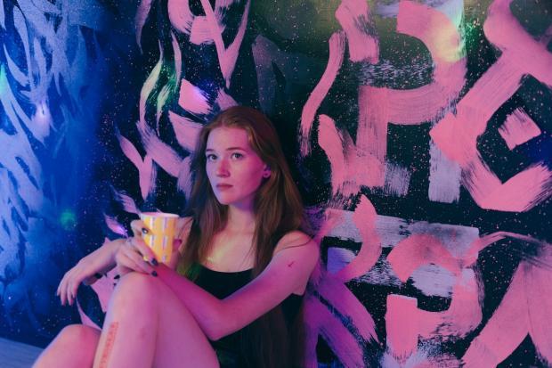 девушка-подросток пьет кофе у раскрашенной стены