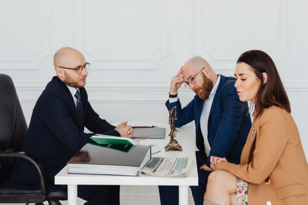 девушка в коричневом пиджаке разговаривает за столом с двумя мужчинами