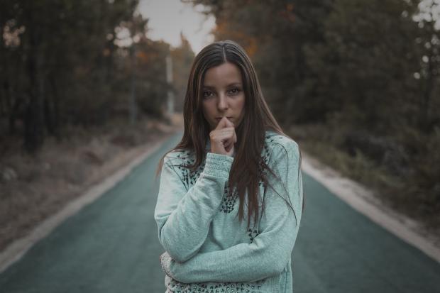 девушка стоит на дороге сложив руки