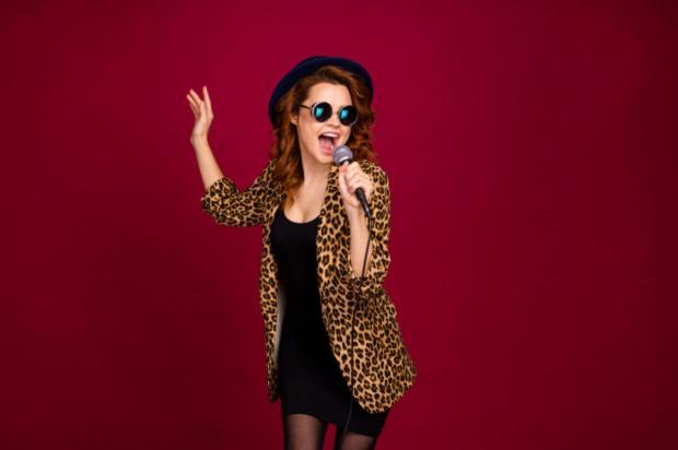 девушка в шляпе и леопардовом пиджаке поет в микрофон