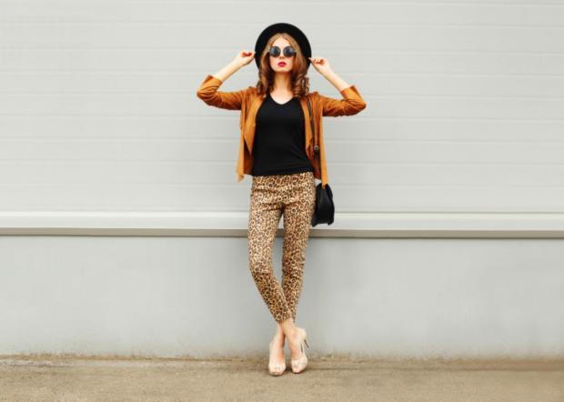 модная девушка в легинсах с леопардовым принтом и шляпке