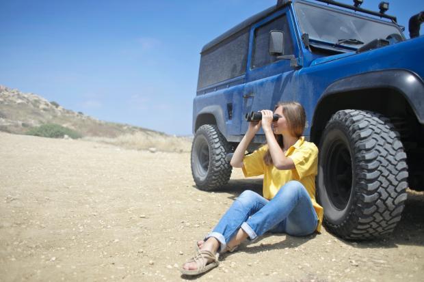 девушка в желтой рубашке сидит рядом с джипом и смотрит в бинокль