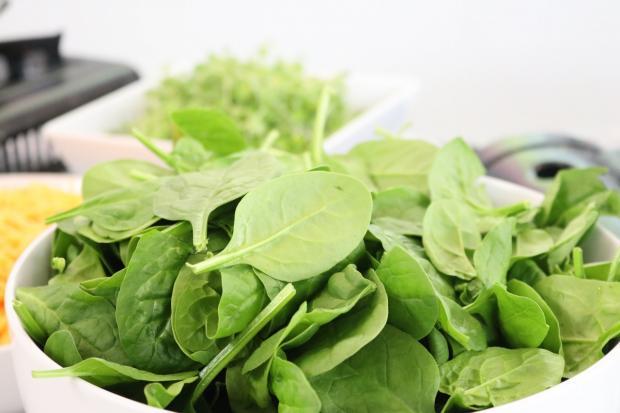 в белой тарелке лежат листы шпината