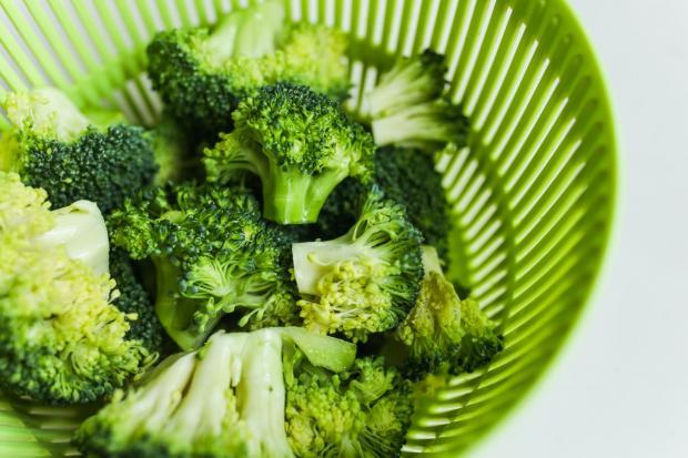 в зеленой тарелке лежат кочанчики брокколи