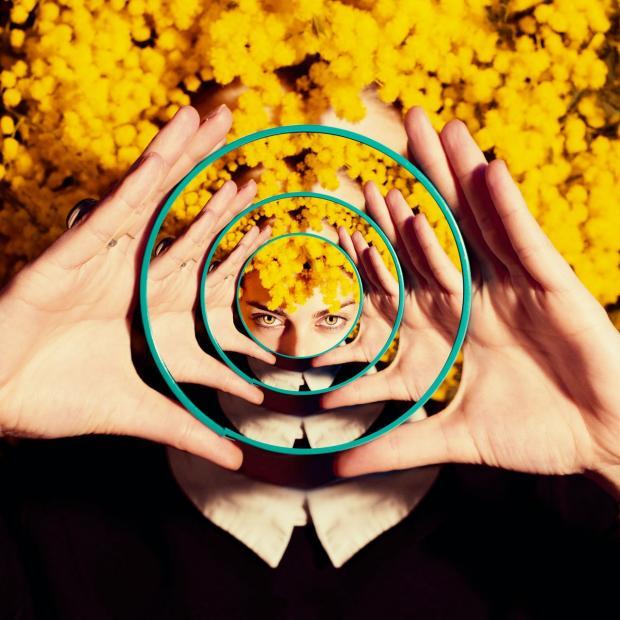 женщина смотрится в круглое зеркало с расходящимися кругами