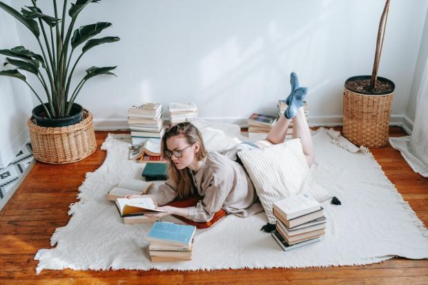 девушка лежит на полу и читает книгу