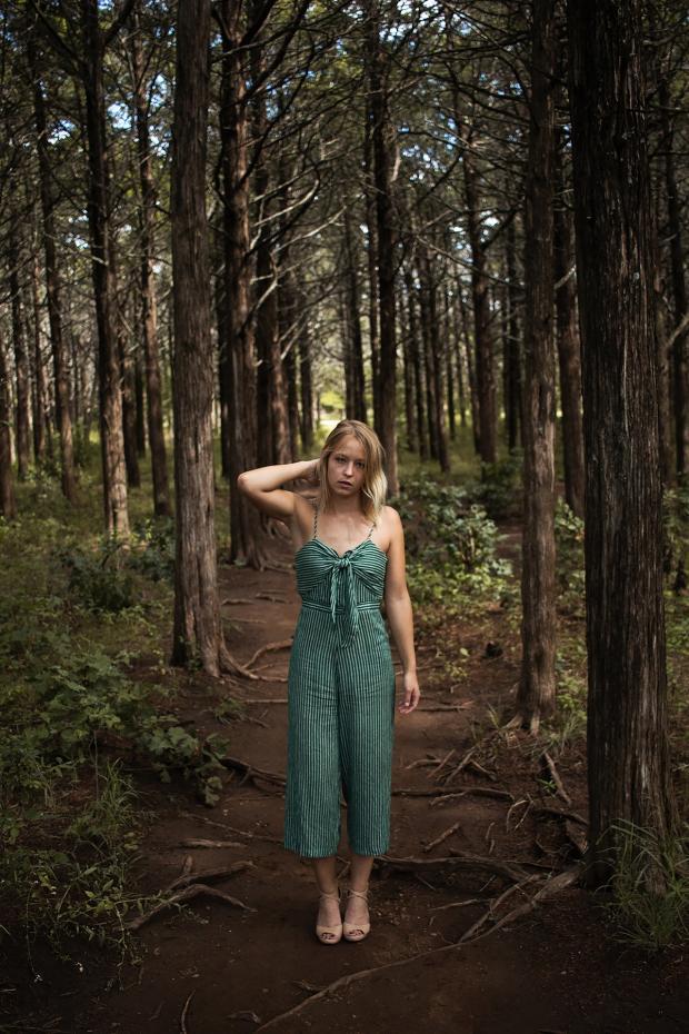 девушка в летнем зеленом комбинезоне заблудилась в лесу