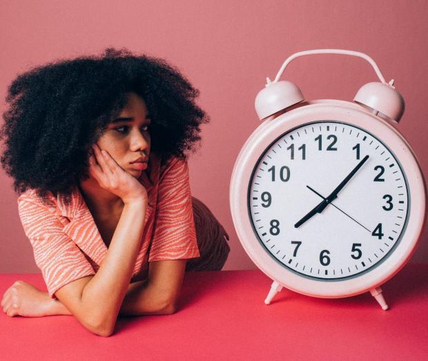 кудрявая брюнетка смотрит на огромный циферблат розового будильника