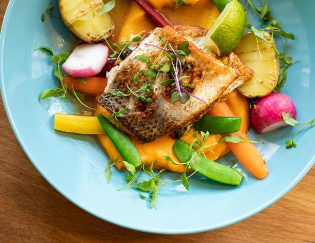 приготовленная с овощами порция рыбы