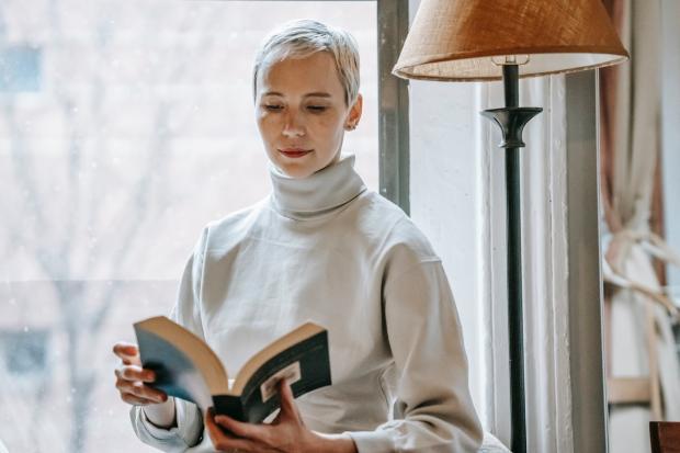женщина с короткой стрижкой и в свитере читает книгу у торшера