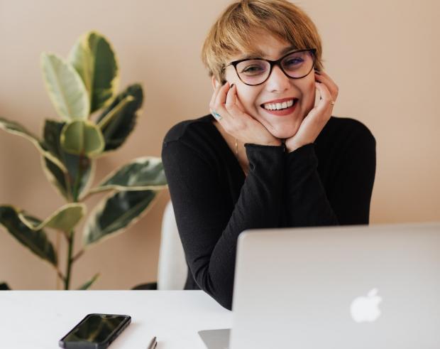 девушка в очках смеется за столом с ноутбуком и смартфоном