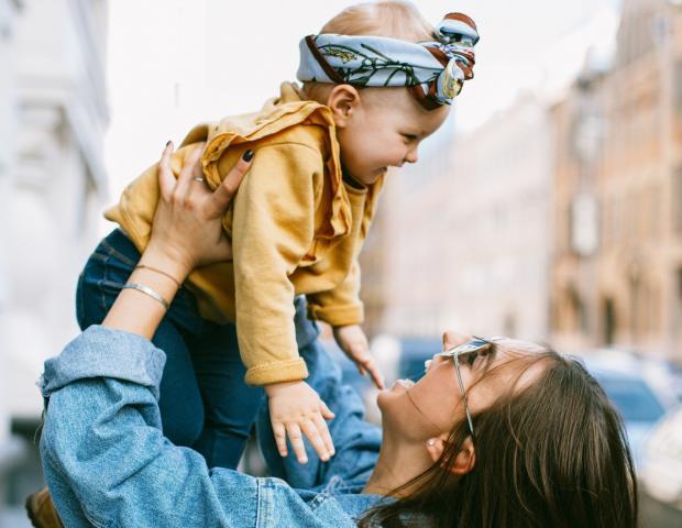 мама держит малыша в желтой кофточке на руках и смеется