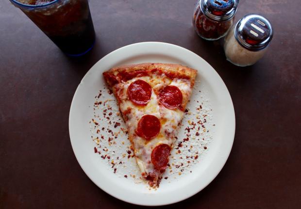 кусочек пиццы на тарелке лежит
