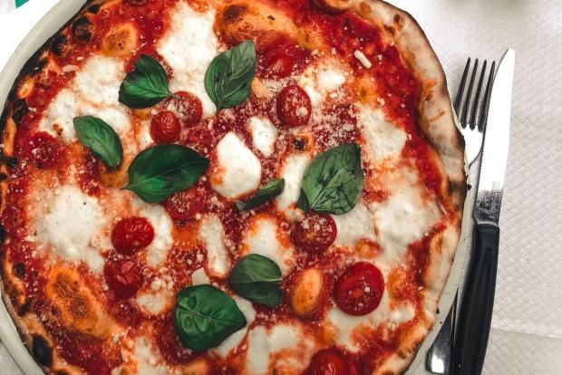 на круглой тарелке лежит пицца
