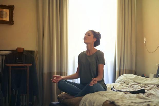 девушка медитирует на кровати