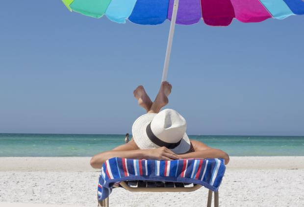 человек лежит на шезлонге на берегу моря