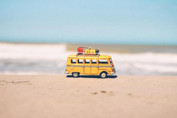 маленькая желтая машинка на песке