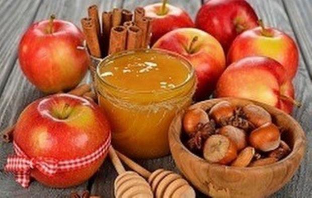 на столе лежат яблоки с медом и орехами