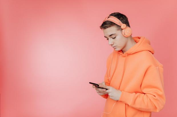 юноша в наушниках смотрит в телефон