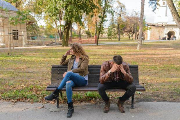 пара сидит отвернувшись друг от друга на скамейке