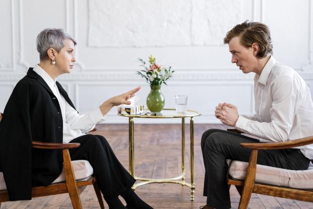 двое сидят на стульях и напряженно разговаривают