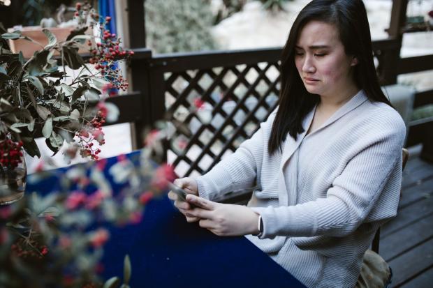 женщина плачет смотря в телефон