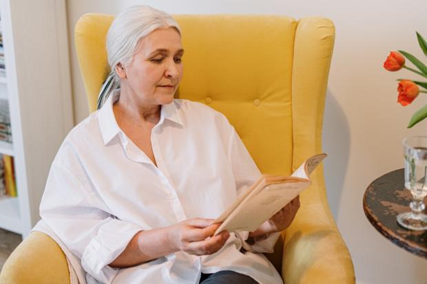 седая женщина читает книгу в желтом кресле