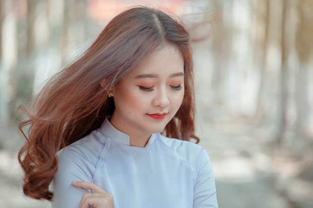 стоит длинноволосая девушка в белой блузке