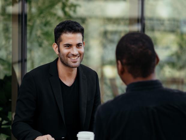 молодой мужчина в черном костюме разговаривает с женщиной