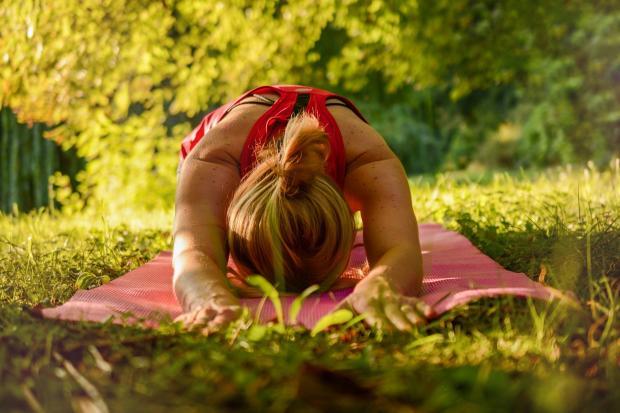 девушка на коврике в парке занимается йогой