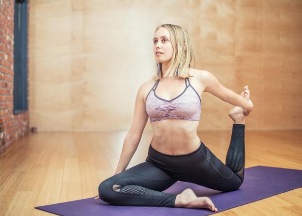 девушка на коврике в позе йоги