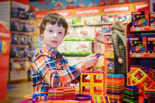 мальчик рассматривает игрушки в магазине
