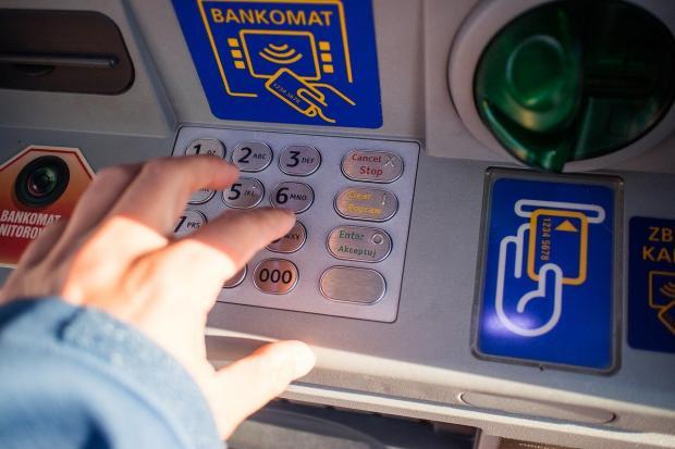человек вводит пин-код на банкомате