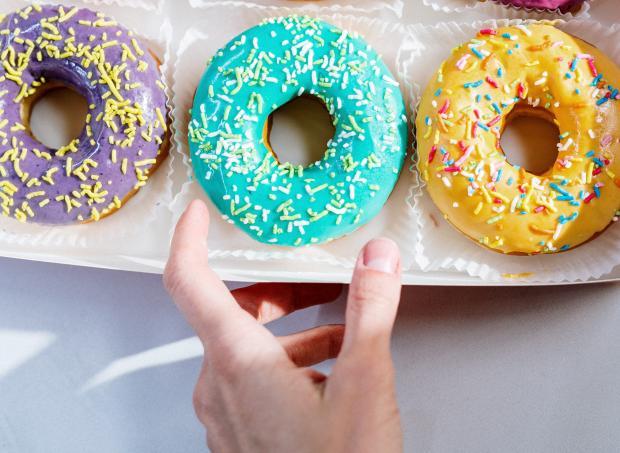 рука женская и яркие пончики
