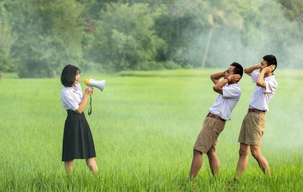 девушка говорит в рупор на зеленом поле