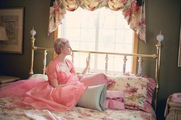 женщина в розовом пеньюаре сидит на винтажной кровати