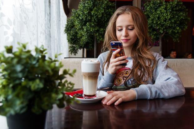 молодая длинноволосая девушка в кафе держит смартфон