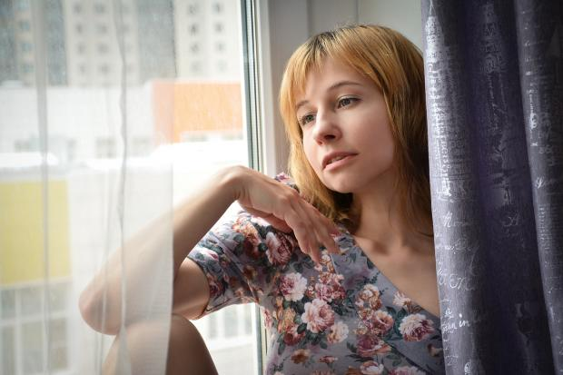 молодая женщина сидит на подоконнике и смотрит в окно