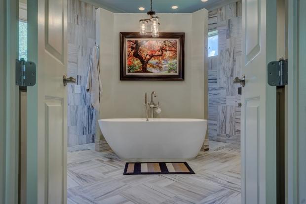 двери распахнуты в красивую ванную комнату с картиной на стене