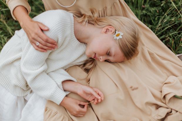 девочка лежит на коленях у мамы
