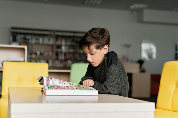 мальчик сидит за столом с книгой