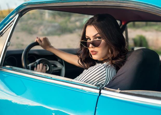 девушка в солнцезащитных очках за рулем автомобиля