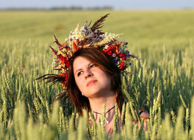 девушка с венком на голове в поле пшеницы