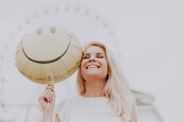 улыбающаяся женщина с воздушным шариком со смайликом