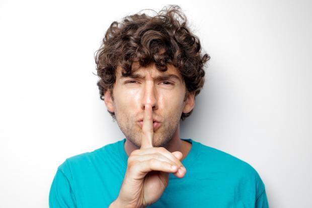 мужчина в голубой футболке приставил палец ко рту