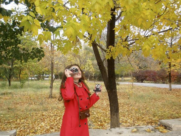 девушка в красном пальто фотографирует осенний пейзаж