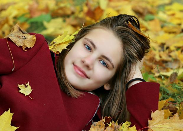 девушка в бордовом пальто лежат на груде осенних листьев